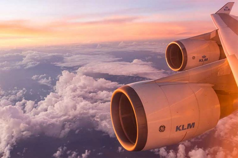 Photo is taken from an aeroplane window. It shows the clouds and sky with a beautiful orange/red tint of sunset and the plan engines.