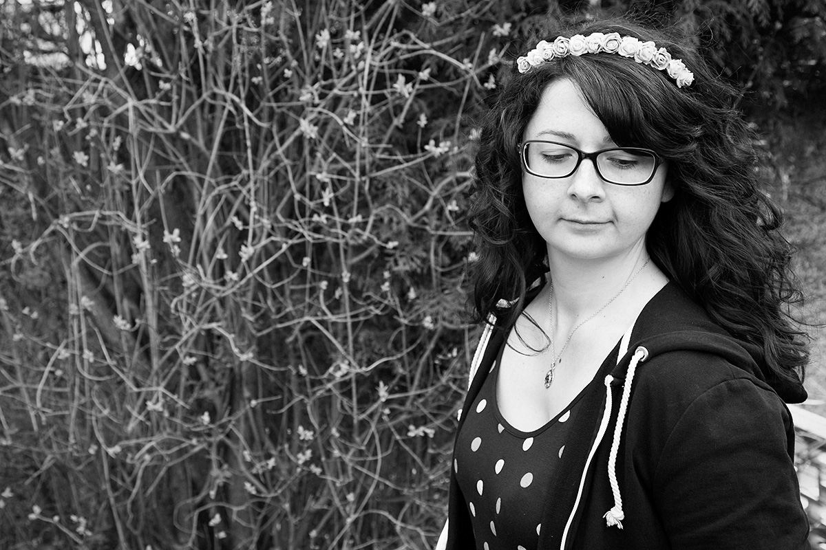A black and white photograph of Donna in the right side of the frame. She has shoulder length curly hair accessorised with a flower crown. She wears glasses and is wearing a polka dot dress and open zipped hoodie. She is looking down.