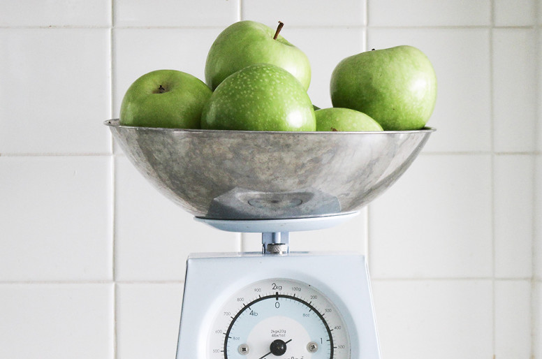 Photo shows green apples being weighed on a scale. The background is square, white tiles.