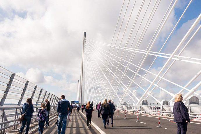 Photograph shows people walking over the Queensferry Crossing with the support tower and cables to the right.