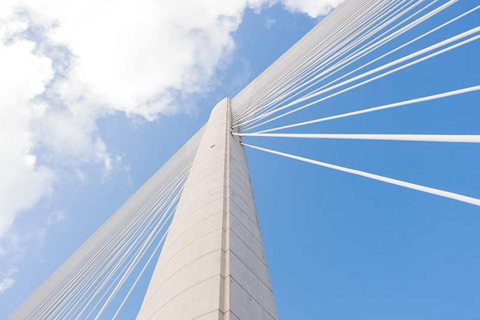 Photograph shows a close-up of one of the supports with the cables spanning from either side.