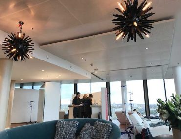 The Infusio, Frankfurt clinic where I had treatment for Lyme Disease. It is a large, bright open space with floor to ceiling windows. The treatment area can be seen which has chaise lounge treatment chairs with IV poles. Three staff members are also in the background preparing treatments.