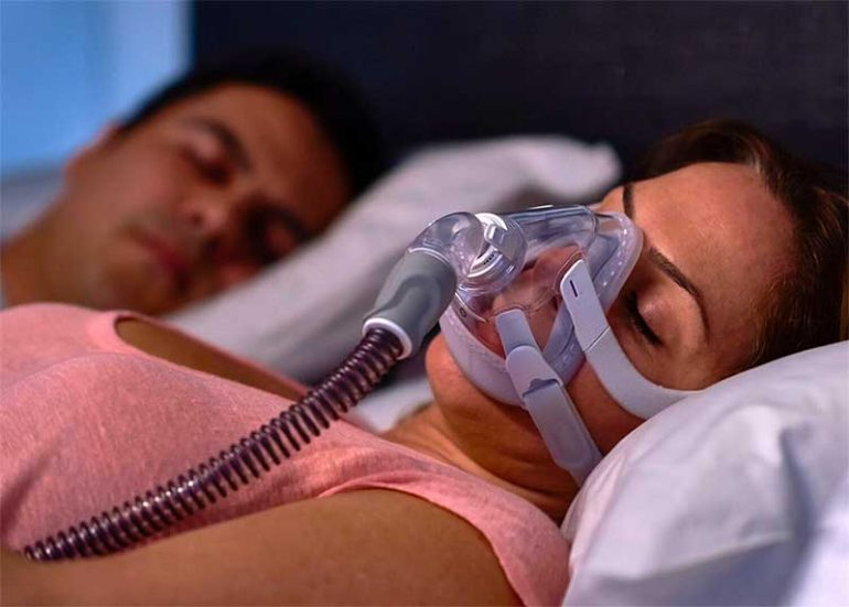 Learn about the connection between sleep apnea and Fibromyalgia and how treatment can help to improve your quality of life. Image shows a woman sleeping wearing a CPAP machine.