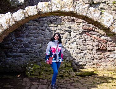 Photograph show Donna standing under an archway at Dunnottar Castle. Why I write about my health online.