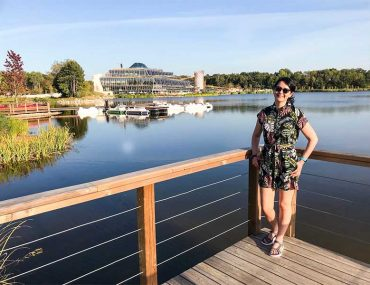 Photo shows Donna standing on a dock by the edge of a lake. She is wearing a leaf print playsuit, sunglasses and her dark hair is tied back in a ponytail. In the distance behind her there is the Aqualagon building at Villages Nature, Paris.
