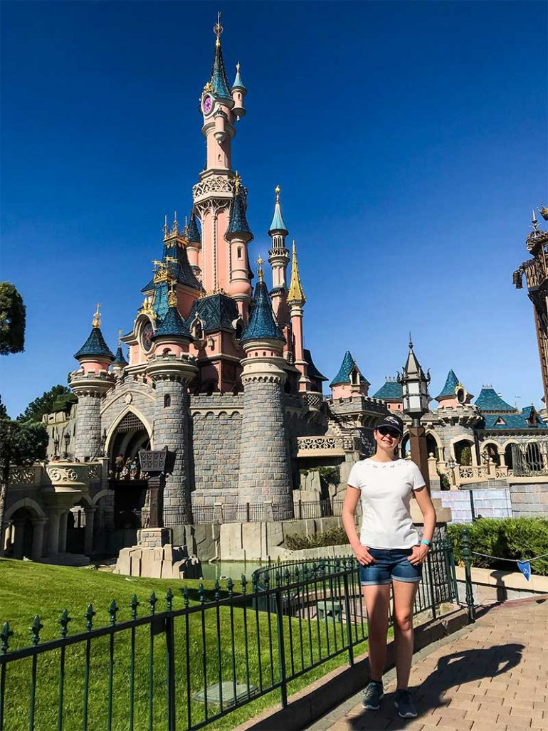 Photo shows Donna standing to the right of the photograph with Sleeping Beauty's castle at Disneyland Paris behind her. Donna is wearing a white t-shirt, denim shorts, sunglasses and a baseball cap.