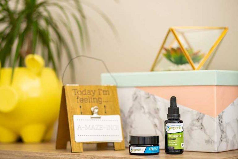 "Photo shows a CBD oil tincture and salve to the right hand sign. Behind them is a decorative cardboard storage box (pink, green and marble), a succulent in a glass terrarium, a plant in a yellow pig planter and a sign that reads ""today I'm feeling amazing""."