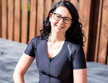 Photo shows Donna wearing the black Active Posture 2.0 with front zip. She is smiling at the camera and has long, dark curly hair and wears glasses. The photo is cropped at her waist.