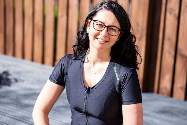 Photo shows Donna wearing the black Active Posture 2.0 shirt with front zip. Donna is looking and smiling at the camera and has long, dark curly hair and wears glasses. The photo is cropped at her waist.