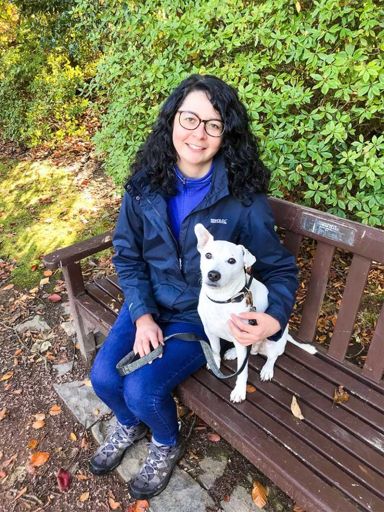 Photo shows Donna, a woman with shoulder-length dark curly hair, sitting on a bench with her dog Oscar, a white Jack Russell Terrier cross sat net to her. She has her arm around him and they are both looking at the camera.