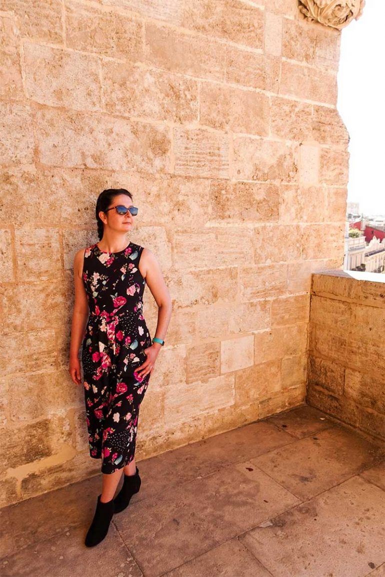 Photo shows Donna stood against a brick wall in the Serrano Towers in Valencia. She wears a black and floral jumpsuit, black ankle boots and dark sunglasses. She has her hair in dutch braid pigtails and is looking off to the right.