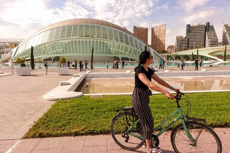 Photo shows Donna sat on a teal bike looking to the right away from the camera. Behind her is a concrete pool of water (water feature) and a building at the City of Arts and Sciences in Valencia that has been designed to resemble a human eye.