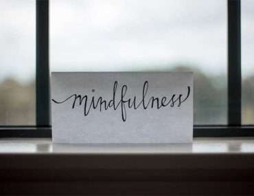 "Photo shows a white piece of paper resting on a windowsill with the word ""mindfullness"" written in a calligraphy style with black ink. There is a window behind the note but the view out of it is blurred."