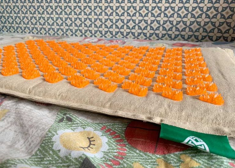 Photo shows a Mindfulness Mat: a linen cushioned mat with orange spiky triangular massagers covering the surface. It is placed on a bed with an owl print duvet and there is a blue/white floral patterned wallpaper behind.