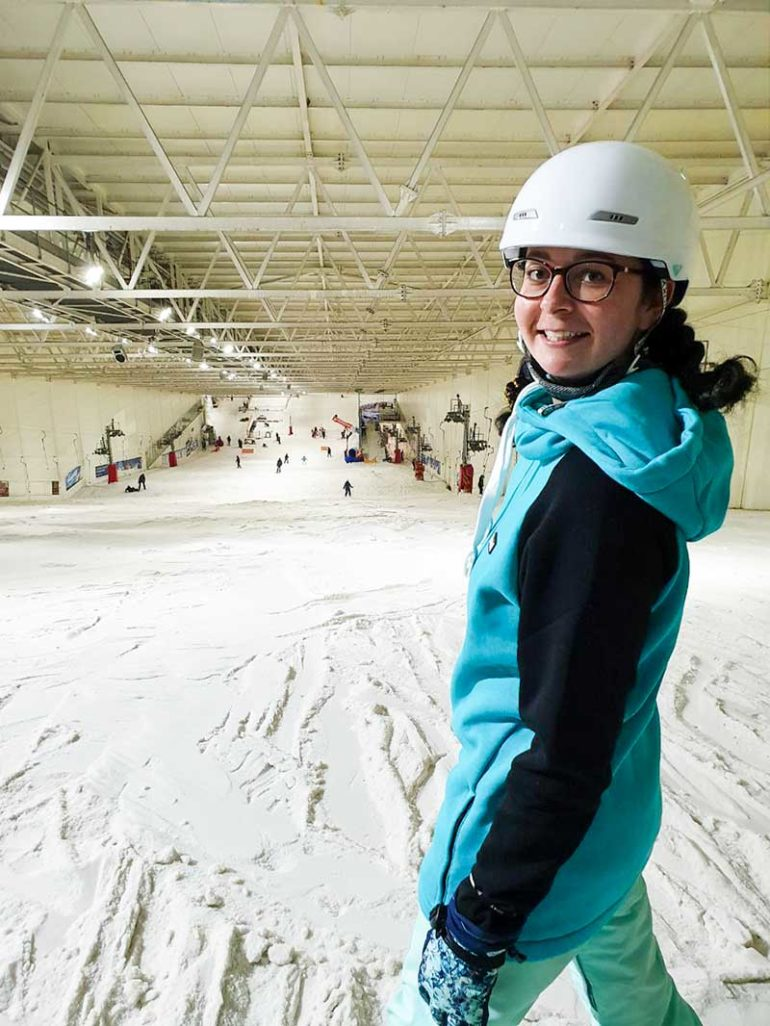 Photo shows Donna stood at the top of the indoor snow slope. She has turned her body towards the camera and is smiling. The photograph is cropped at her knee so you cannot see the snowboard attached to her feet. Donna wears a teal hoodie with black sleeves and a white helmet. Her dark hair is braided.
