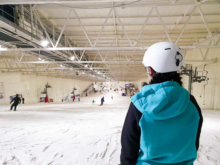 Photo is taken from behind Donna at the top of the indoor snow slope. The photo is cropped at her waist and Donna is looking ahead, down the slope. Donna wears a teal hoodie with black sleeves and a white helmet.