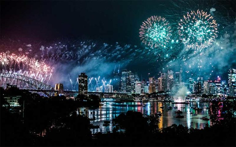Photograph shows fireworks over a river with the silhouette of a bridge and city in the background.